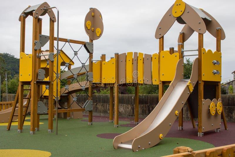 Campo de jogos vazio colorido no parque Parque amarelo e marrom do divertimento para crianças foto de stock