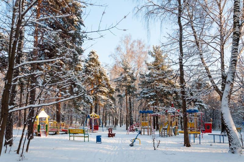 Campo de jogos vazio das crianças na floresta no inverno imagem de stock royalty free