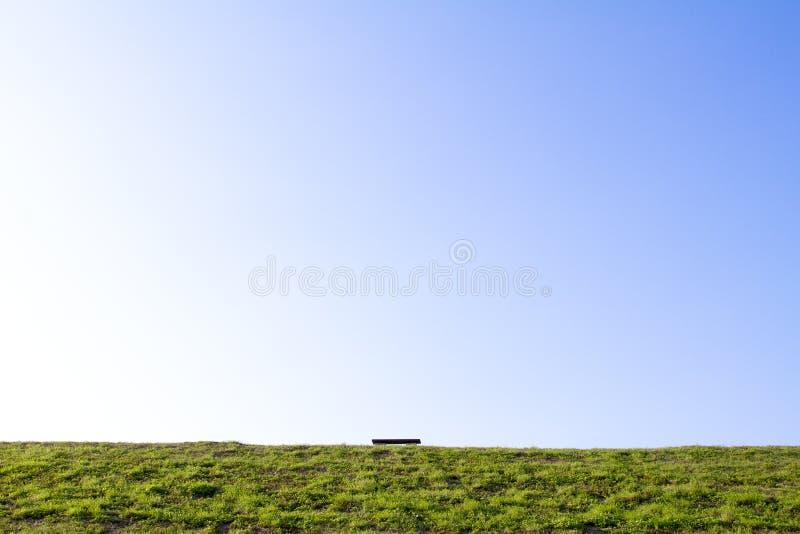 Campo de la hierba y del cielo perfecto con el banco imágenes de archivo libres de regalías