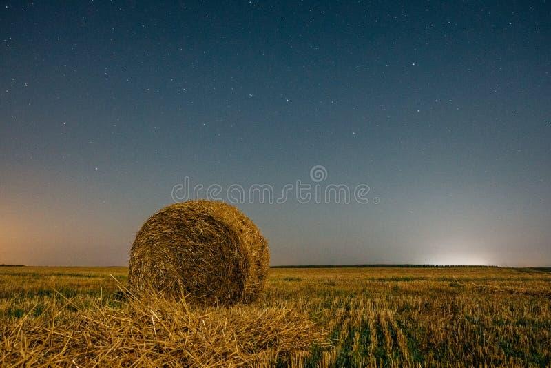 Campo de la noche con un pajar debajo de un cielo nocturno hermoso foto de archivo