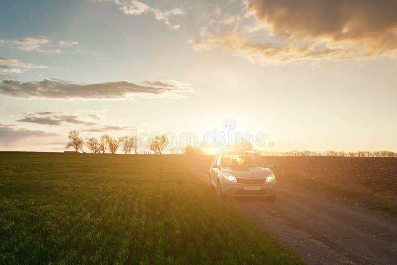 Campo de primavera y coche en camino de tierra al atardecer fotos de archivo libres de regalías
