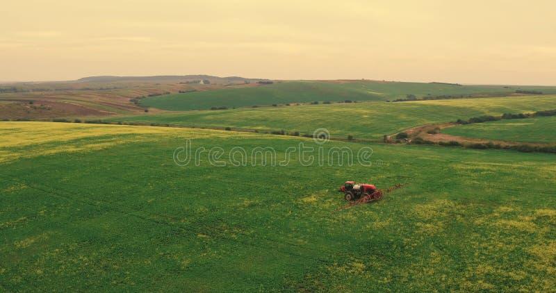 Campo de pulverização do trator Campo de trigo de pulverização da colheita do verão do trator da agricultura imagens de stock royalty free