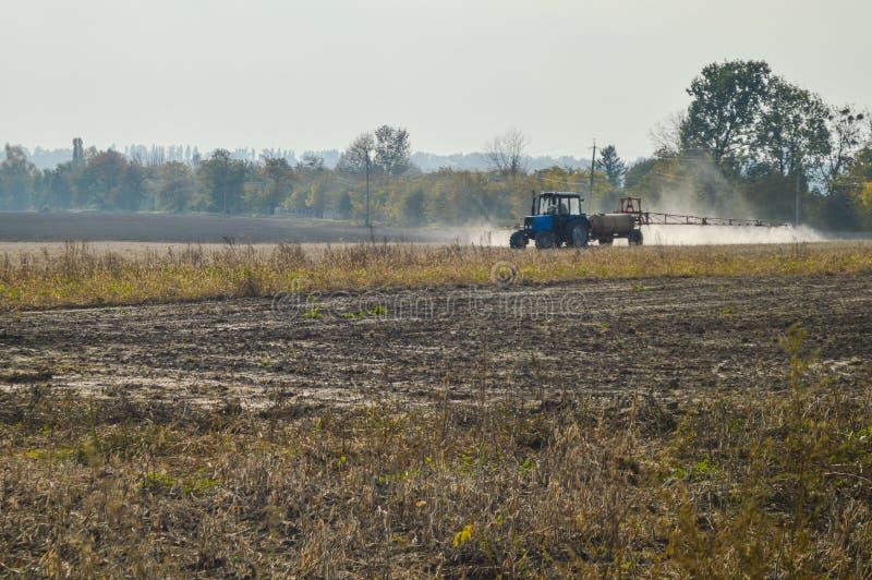 Campo de rociadura del otoño del tractor foto de archivo libre de regalías