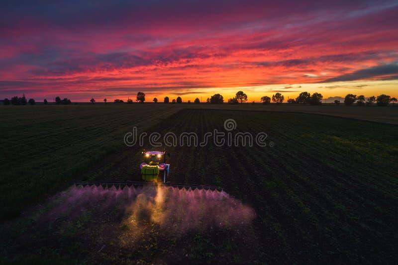 Campo de rociadura del tractor en la primavera, opini?n a?rea de la puesta del sol imagen de archivo libre de regalías