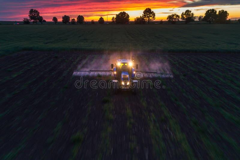 Campo de rociadura del tractor en la primavera, opini?n a?rea de la puesta del sol foto de archivo
