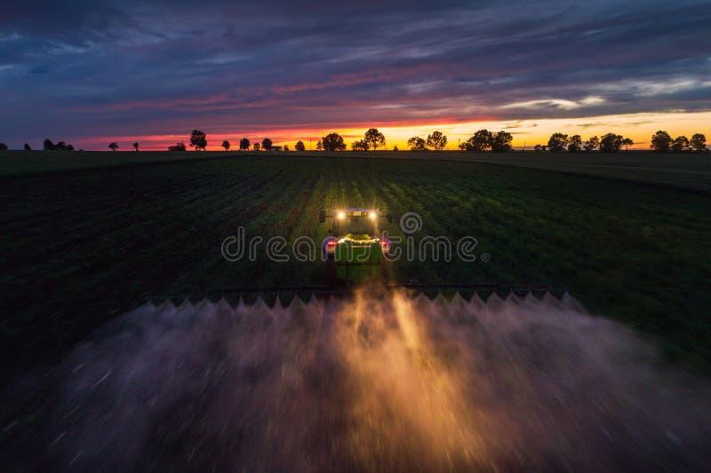 Campo de rociadura del tractor en la primavera, opini?n a?rea de la puesta del sol imagenes de archivo