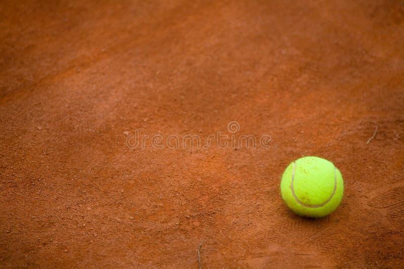 Campo de tenis y tennisball de la arcilla fotografía de archivo libre de regalías