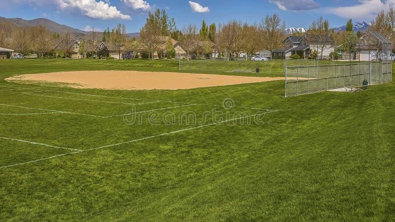 Campo del béisbol o de softball del marco del panorama con los edificios y los árboles más allá del terreno herboso fotos de archivo libres de regalías
