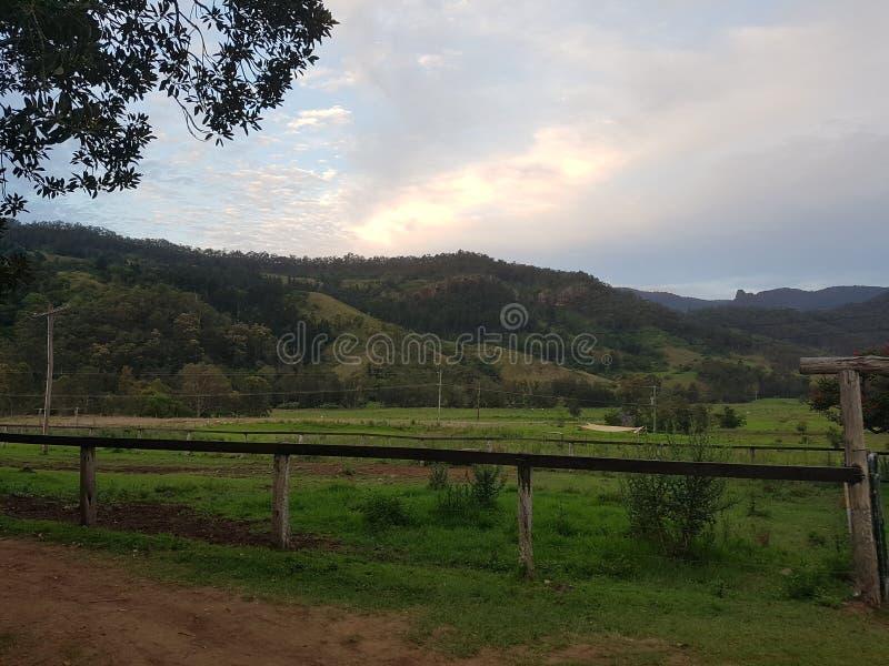 Campo del campo en la puesta del sol con la cerca de madera imagen de archivo