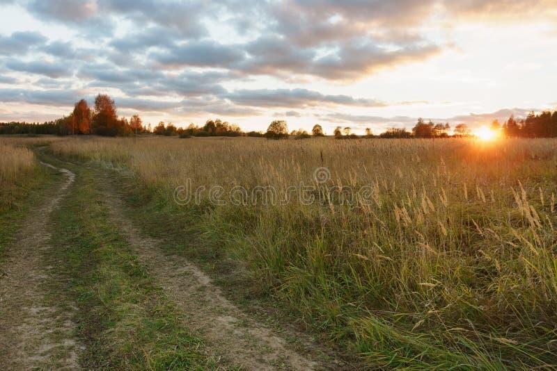 Campo del otoño en los suburbios en la puesta del sol imagenes de archivo