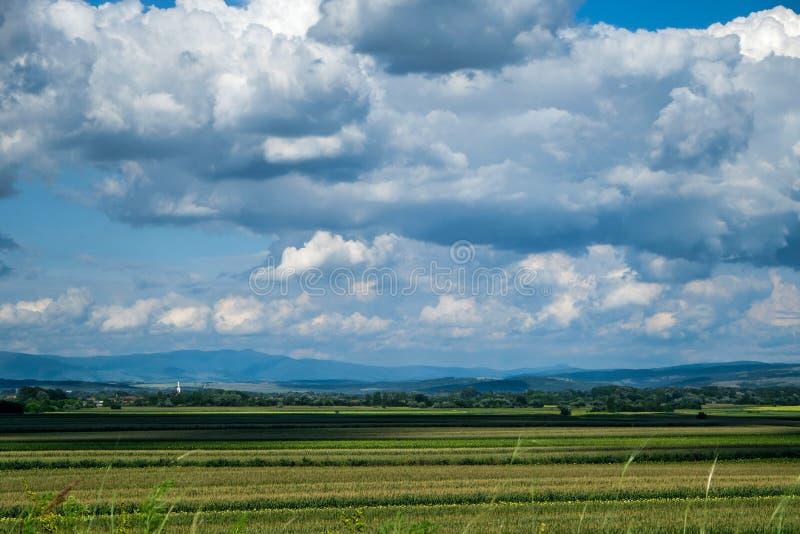 Campo dell'azienda agricola con Cloudscape e le montagne immagine stock libera da diritti
