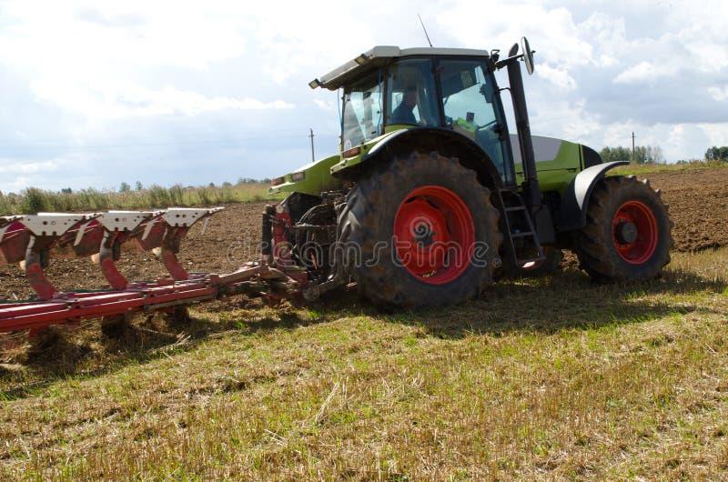 Campo di agricoltura del solco dell'aratro del primo piano del trattore fotografia stock