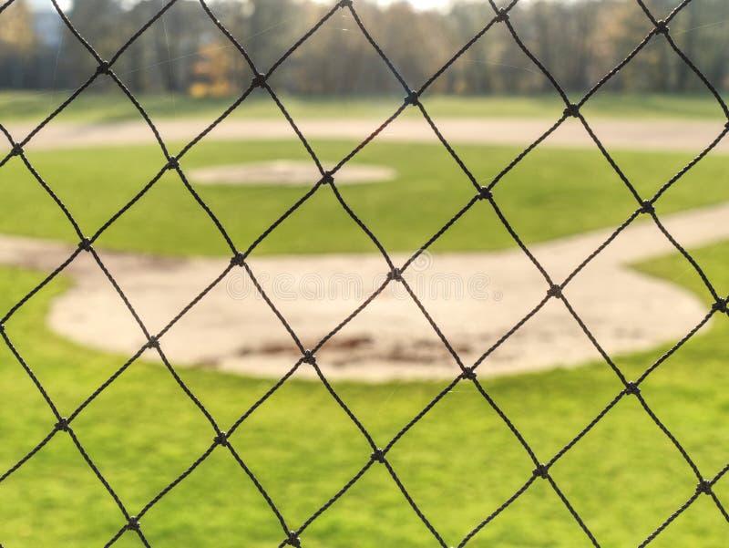 Campo di baseball della gioventù osservato da dietro rete fotografia stock
