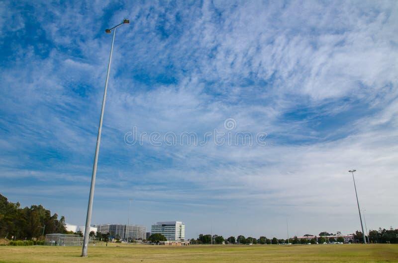 Campo di erba verde con il cielo nuvoloso blu e riflettore alto per l'avvenimento sportivo di notte immagine stock libera da diritti