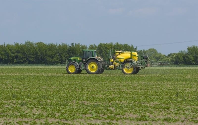 Campo di fertilizzazione del trattore fotografia stock libera da diritti