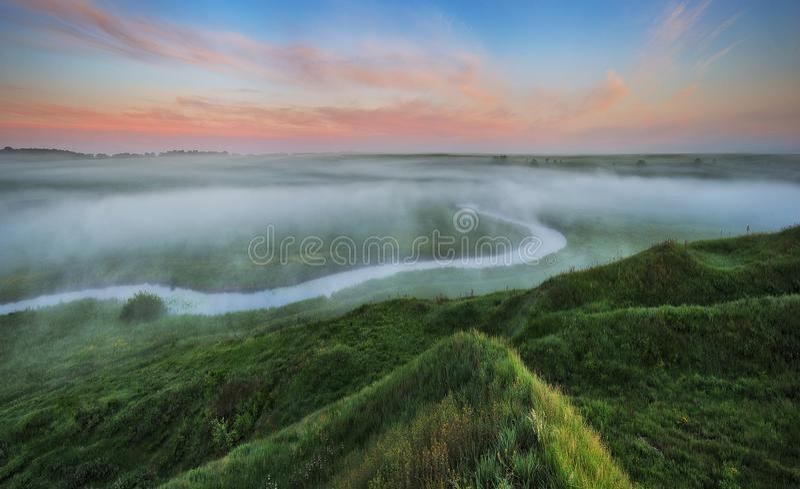 Campo di mattina della sorgente? di erba verde e del cielo nuvoloso blu Alba nella valle del fiume pittoresco immagine stock