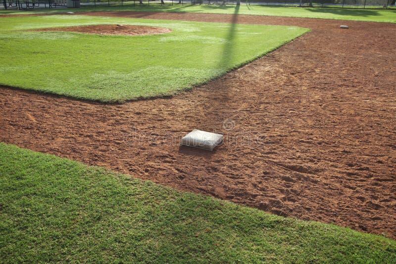 Campo do basebol da juventude do lado da primeira base na luz da manhã fotos de stock
