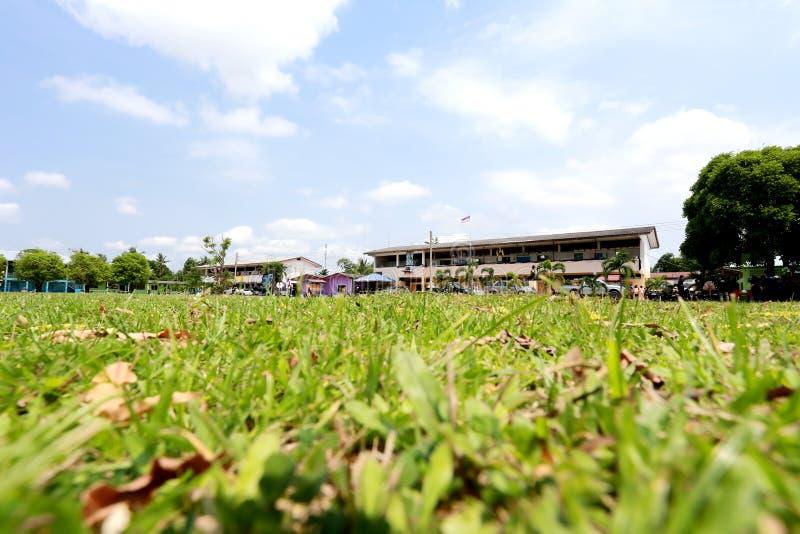 Campo e cielo blu verdi della vista della scuola fotografia stock