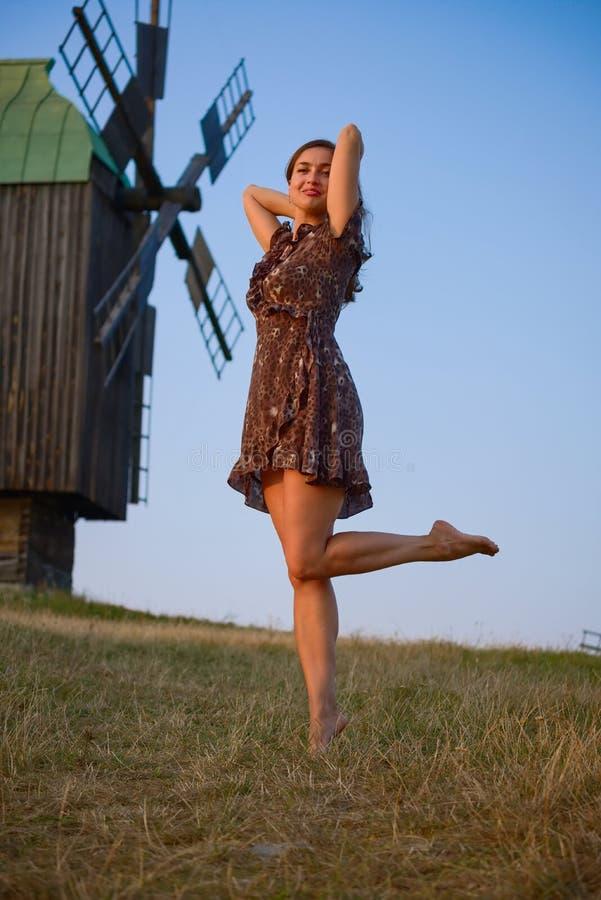 Campo e moinho de vento bonitos de dança da menina fotografia de stock royalty free