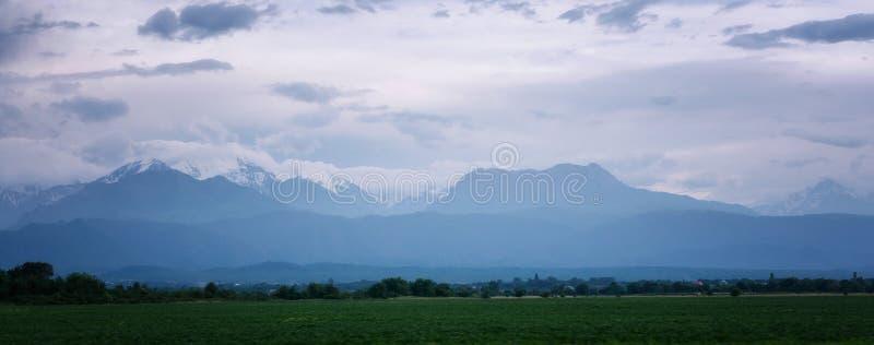 Campo e opinião do panorama em montanhas de Cáucaso, perto da montanha de Elbrus fotografia de stock royalty free