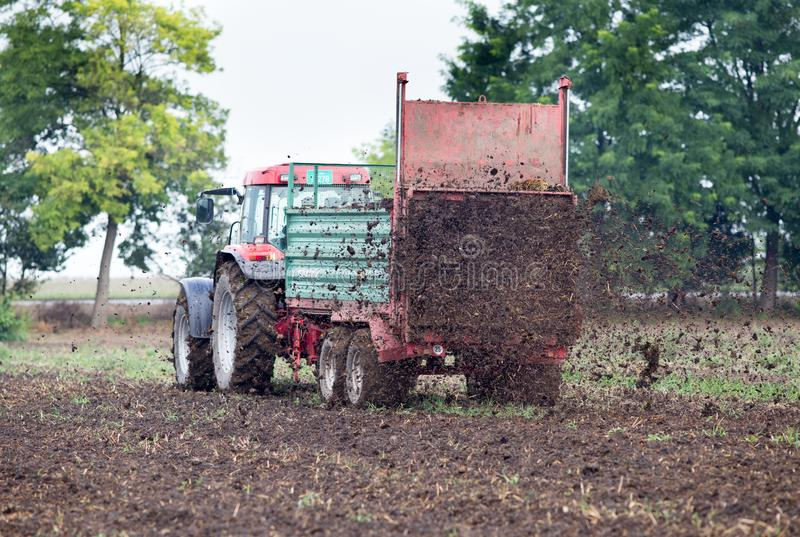 Campo fertilizzante del trattore con fusto immagini stock libere da diritti