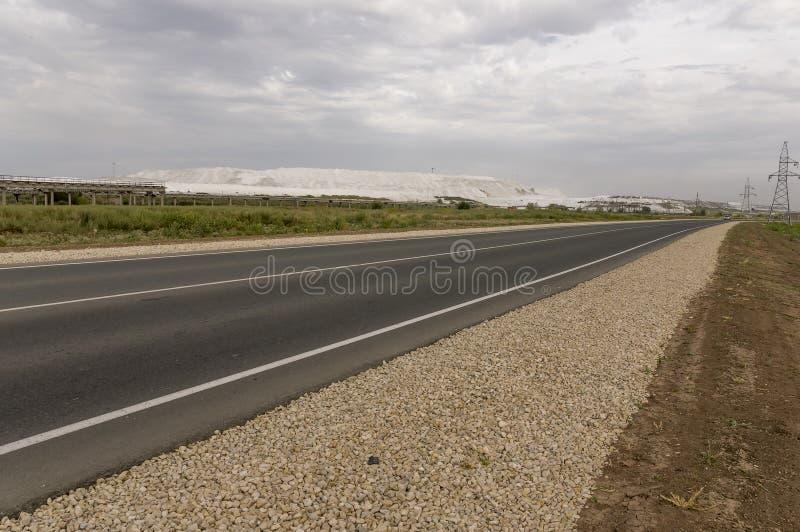 Campo grande del oto?o con los ?rboles lejos y las nubes en el cielo azul Carretera de asfalto travelling fotografía de archivo