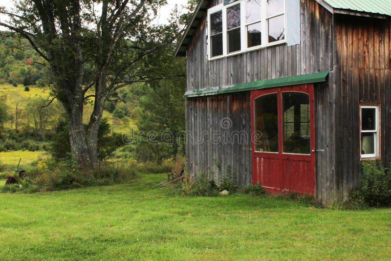 Campo herboso con el pequeño granero convertido con las puertas y las ventanas rojas imagen de archivo libre de regalías