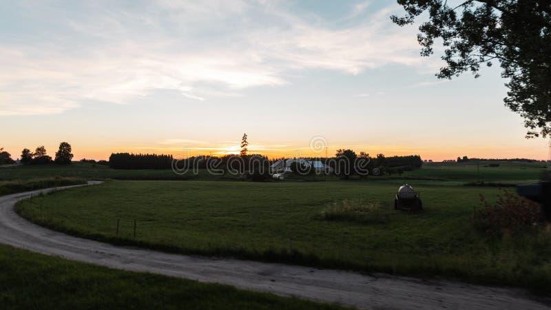Campo hermoso del paisaje del verano en la puesta del sol Trayectoria al pueblo Gran hogar del día de fiesta en el campo tarde imagenes de archivo
