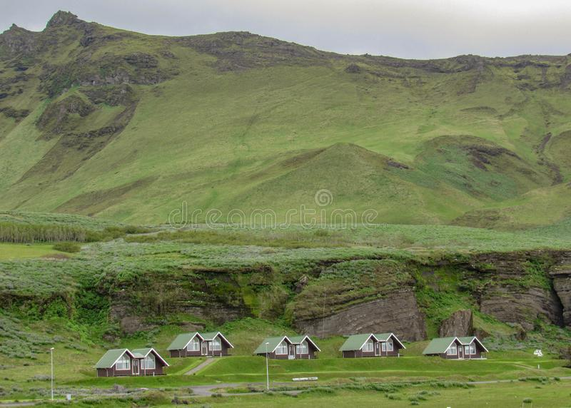 Campo islandês com as casas e as montanhas minúsculas pequenas no fundo em Islândia sul, Europa imagens de stock royalty free