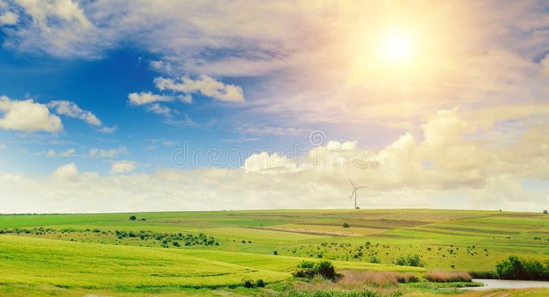 Campo, molino de viento y sol verdes montañosos en fondo del cielo azul wide imagen de archivo libre de regalías