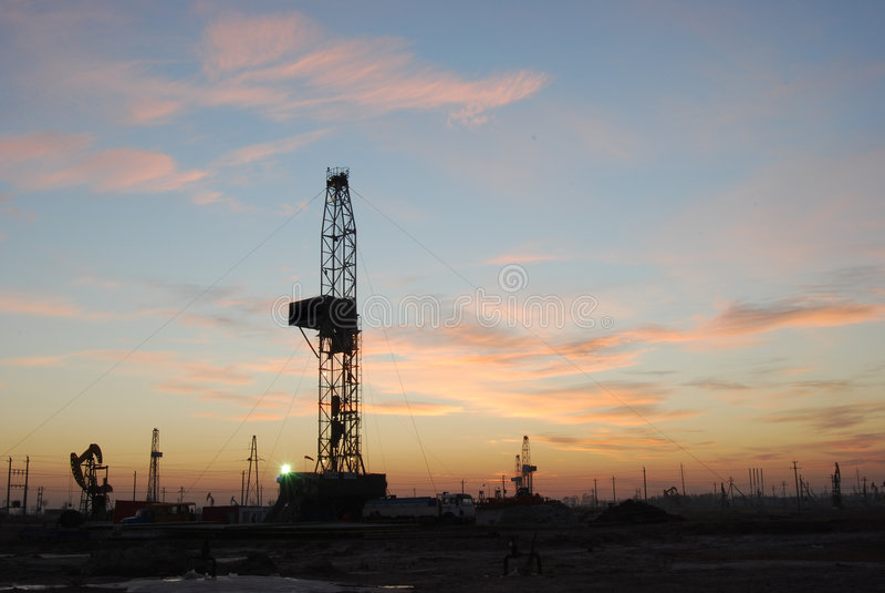Campo petrolífero o fulgor de noite fotografia de stock