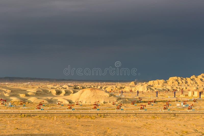 Campo petrolífero ventoso de la ciudad de Xinjiang en puesta del sol fotografía de archivo