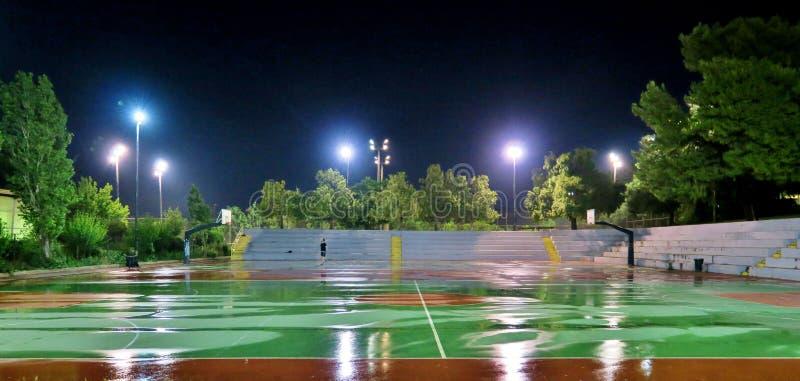 Campo rosso e verde di pallacanestro dopo la pioggia fotografia stock