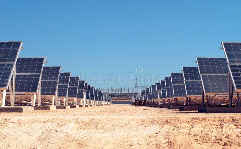 Campo solar con la estación de la energía eléctrica en el fondo fotos de archivo