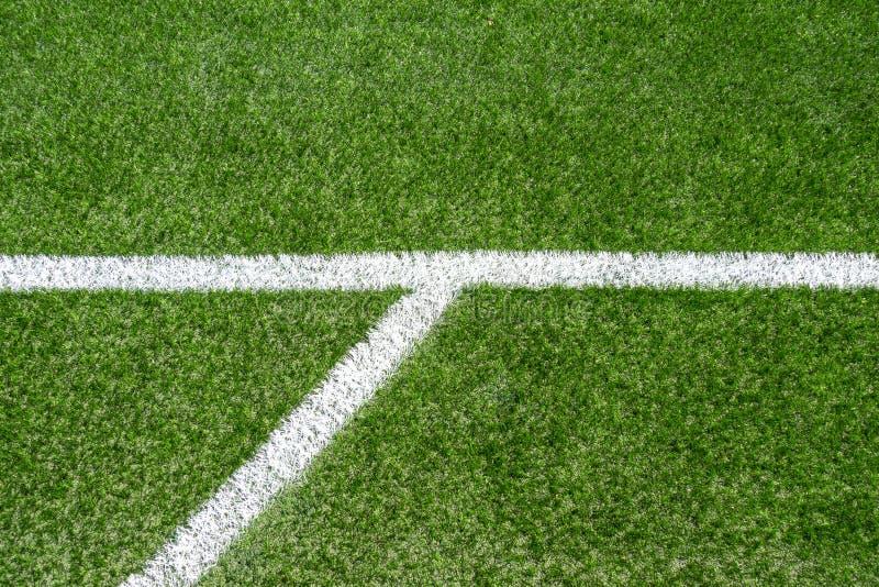 Campo sportivo artificiale sintetico verde di calcio dell'erba con la linea d'angolo bianca della banda immagini stock
