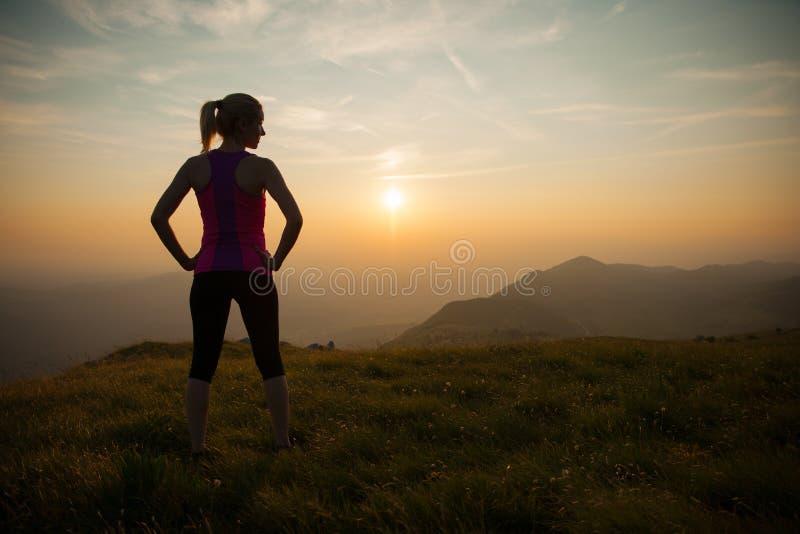 Campo a través hermoso de los runns de la mujer joven en una trayectoria mountian en fotografía de archivo libre de regalías