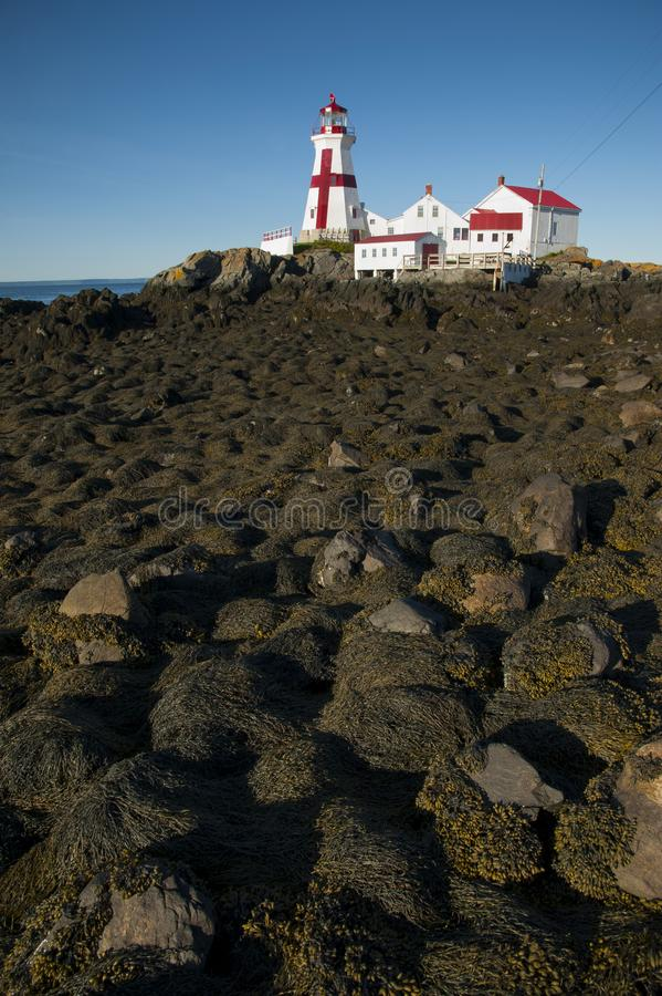 Slippery Rocks Lead to Canadian Lighthouse stock image