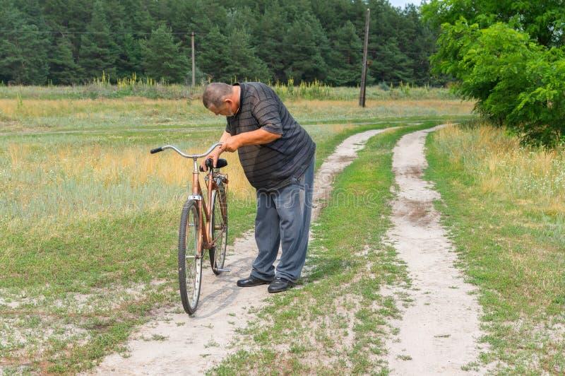 Camponês que está em uma estrada secundária e que inspeciona a bicicleta oxidada velha fotos de stock royalty free