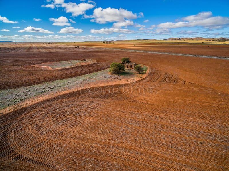 Campos alaranjados arados e ruínas velhas da construção foto de stock