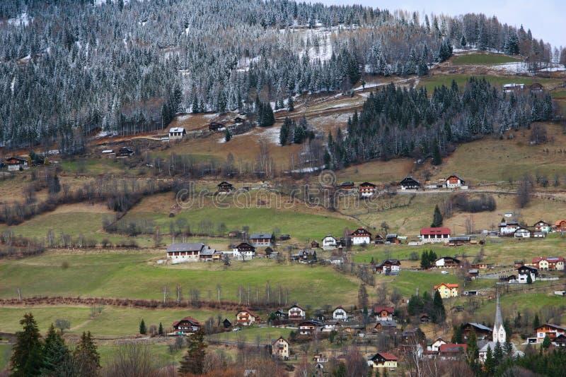 Campos alpinos de la primavera y casas de madera tradicionales imagenes de archivo