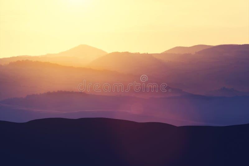 Campos brumosos y colinas rurales durante la puesta del sol imagen de archivo libre de regalías