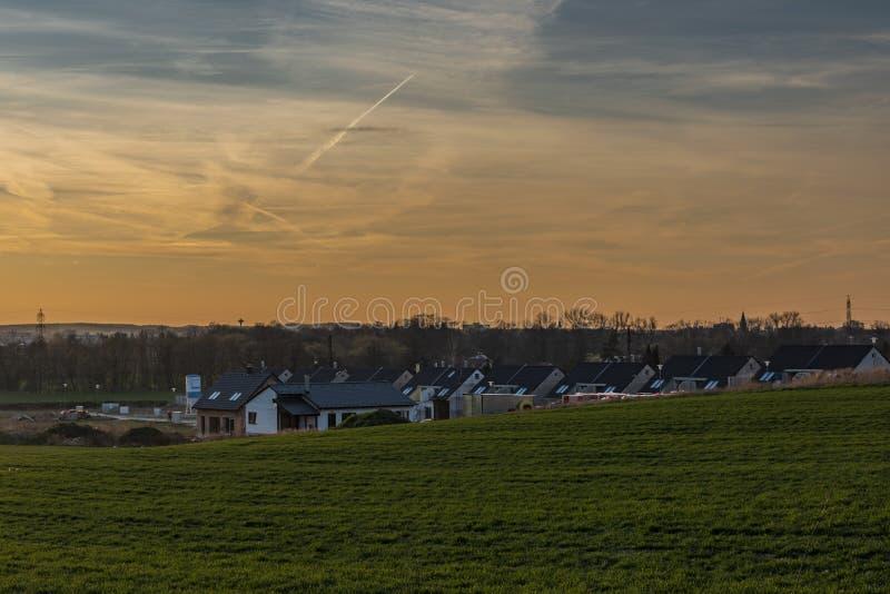 Campos de color y cielo azul en tiempo de la puesta del sol cerca de Ceske Budejovice con las nuevas casas imagenes de archivo