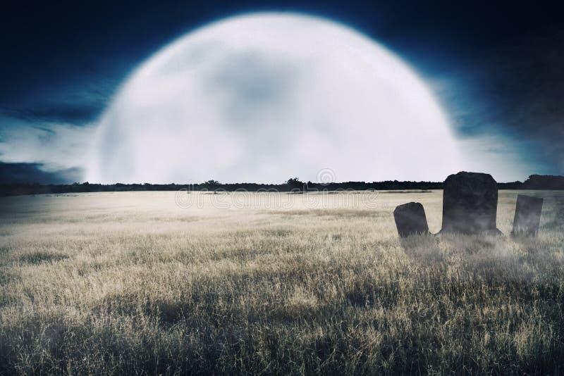 Campos de hierba espeluznantes con los sepulcros y piedra sepulcral en la medianoche foto de archivo libre de regalías