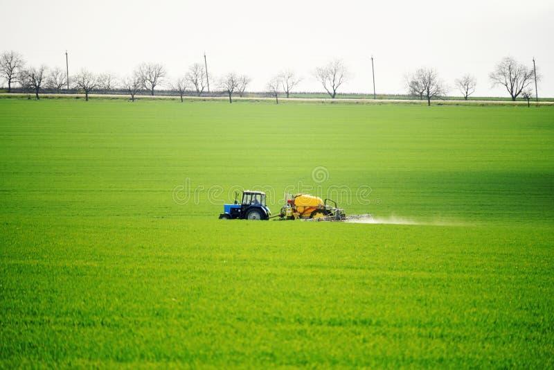 Campos verdes en resorte El tractor realiza el trabajo en el terreno de la primavera fotos de archivo libres de regalías