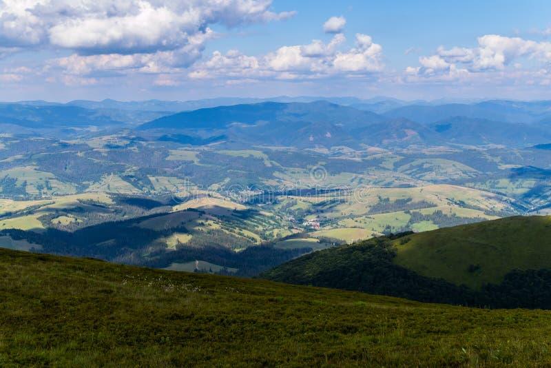 Campos verdes, florestas decíduos e uma vila rural pequena no pé da cimeira de uma montanha enorme imagem de stock royalty free