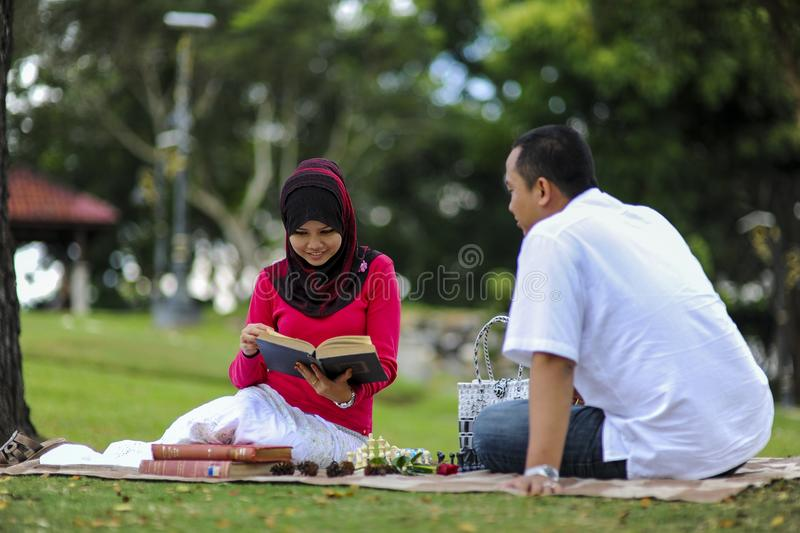 Campus life, student`s love. Beautiful couple learning together in the park. Education, love and tenderness, dating, romanc. E in Malaysia royalty free stock image