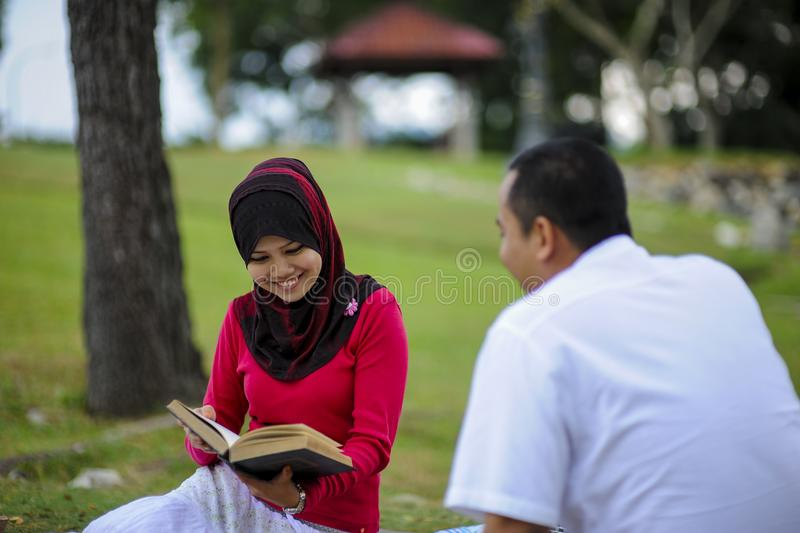 Campus life, student`s love. Beautiful couple learning together in the park. Education, love and tenderness, dating, romanc. E in Malaysia royalty free stock photo