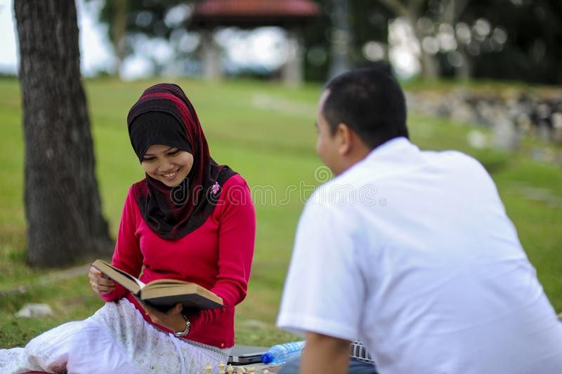 Campus life, student`s love. Beautiful couple learning together in the park. Education, love and tenderness, dating, romanc. E in Malaysia royalty free stock photos