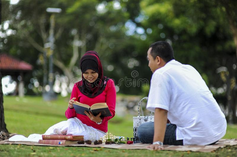 Campus life, student`s love. Beautiful couple learning together in the park. Education, love and tenderness, dating, romanc. E in Malaysia royalty free stock images