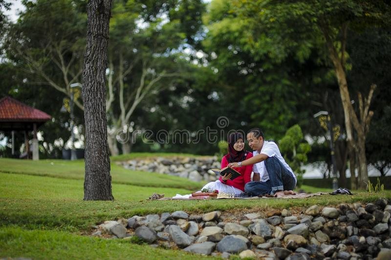 Campus life, student`s love. Beautiful couple learning together in the park. Education, love and tenderness, dating, romanc. E in Malaysia stock images